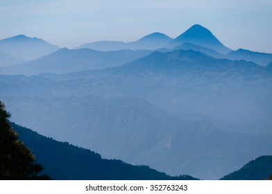 Branches in front of far away cold blue mountains with mist and fog close to Quetzaltenango in Guatemala