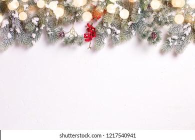 Zweige Fellbaum und rote Beeren auf weißem strukturiertem Hintergrund mit Bokeh-Lichtern.Draufsicht. Selektiver Fokus. Platz für Text.