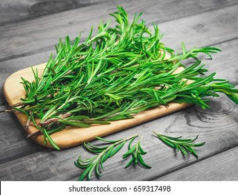 Branches of rosemary on gray wooden table.  Rosemary on cutting board. Rustic style, fresh organic herbs.