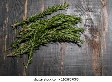 branches of spice rosemary lies on a dark wooden board. background with a plant