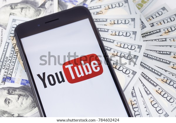 Brand black Apple iPhone 8+ with YouTube logo and money. YouTube is a free video sharing application that anyone can watch. Ekaterinburg, Russia - January 1, 2018