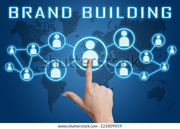 Brand Building concept with hand pressing social icons on blue world map background.