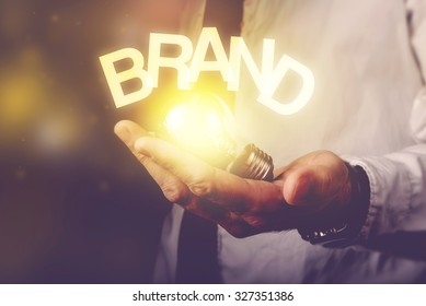 Brand idea concept with businessman holding light bulb, retro toned image, selective focus.