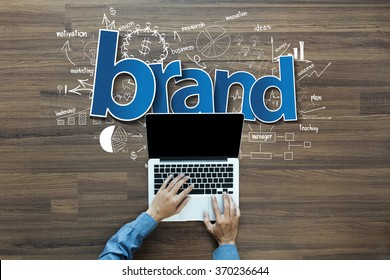Brand identity ideas concept, Creative thinking drawing charts and graphs strategy plan on wooden table background, Inspiration concept with businessman working on laptop computer PC, Top View