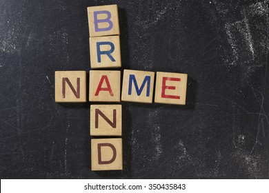 Brand Name Crossword with wooden block on the blackboard