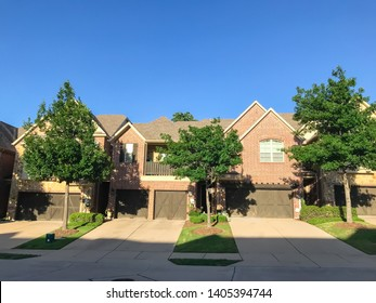 Brand new attached houses townhome style with double wooden garage doors, small front yard. Townhouse units in suburban Dallas, Texas, USA. Front view facade of two stories house nice trim landscape