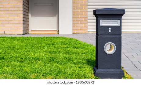 Brand new Australian house freestanding mailbox on green lawn at front yard