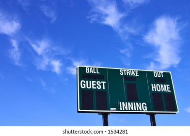Brand new baseball scoreboard and a brilliant blue sky with wispy clouds.