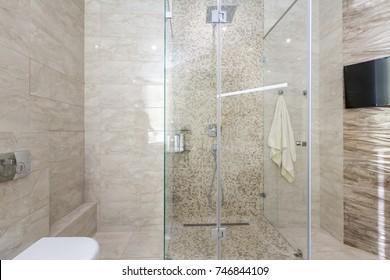 Brand new bathroom interior design. Luxury modern bathroom with white bath tub, washing machine, walk in shower with glass door.
