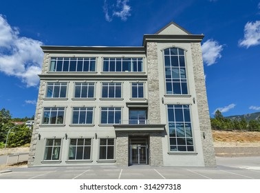 Brand new commercial building with retail and office space available for sale or lease. New office building with parking stalls in front and blue sky background awning opening.