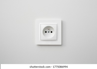 Brand new electrical socket isolated on gray wall. Renovated studio apartment power supply background. Empty copy space white plastic power outlet.