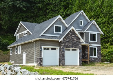Brand new family house with gravel driveway on country side in British Columbia, Canada. Brand new house with green forest background