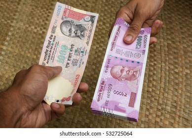 The brand new Indian currency notes of 2000 and old 1000 rupees holding in women hand. Exchange the old by new currency notes.
