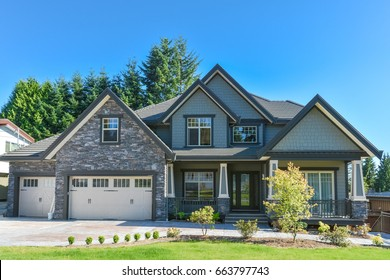 Brand new luxury residential house with big garage for three cars. Family house with concrete driveway and green lawn in front