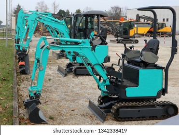 Brand new mini excavators lined up outdoors