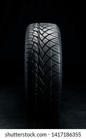 Brand new modern car tyre on a black background. Studio shot