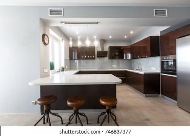 Brand new modern kitchen. Open space kitchen and white counter top, brown cupboard, leather stool, hardwood floor, black stove, stainless fridge. Kitchen interior design. Luxury kitchen furniture.