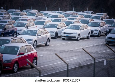 Brand new motor vehicles in a parking lot waiting for export