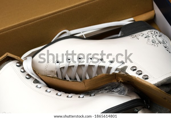 Brand new pair of white figure skates for women in the opened box. Selective focus.
