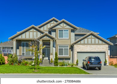 Brand new residential house with car parked on driveway in front. Big family house with double garage door and blue sky background. British Columbia, Canada.