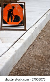 Brand new sidewalk with focus on an orange construction worker sign.