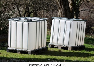 Brand new two intermediate bulk containers or IBC plastic tanks with metal cage used for water storage put on wooden pallets in local garden surrounded with grass and trees on warm sunny spring day