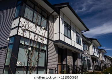 Brand new upscale townhomes in a Canadian neighbourhood. External facade of a row of colorful modern urban townhouses.brand new houses just after construction on real estate market