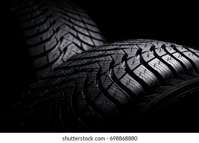 Brand new winter tires with a modern tread on the black background