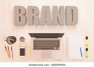 Brand - text concept with notebook computer, smartphone, notebook and pens on wooden desktop. 3D render illustration.