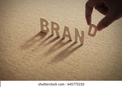 BRAND wood word on compressed or corkboard with human's finger at D letter.