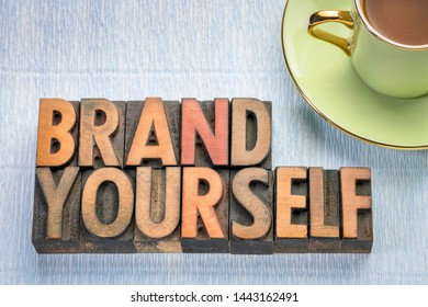 brand yourself word abstract in vintage letterpress wood type with a cup of coffee