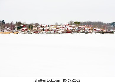 Brandaholm (Karlskrona, Sweden) allotment village with small red cabins in winter landscape. Frozen sea covered in snow in the foreground.