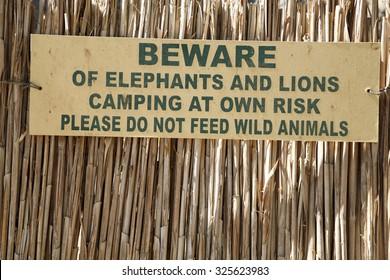 BRANDBERG, NAMIBIA, DECEMBER 15: Wooden sign board warning visitors to beware of lions, elephants and wild animals outside the campsite. Namibia, 2006