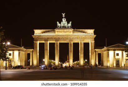 Brandenburg tor during night. Artist is playing with fire in front.