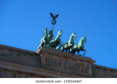 Brandenburger Tor Berlin. Statue on top of Brandenburger Tor with blue sky. Tourist attraction in Berlin. History of Berlin.