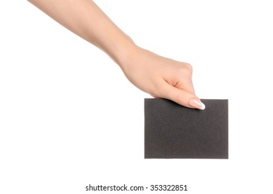 Branding and advertising theme: beautiful female hand holding empty black paper card isolated on white background