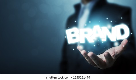 Branding idea concept. Businessman hand holding word BRAND with bokeh background