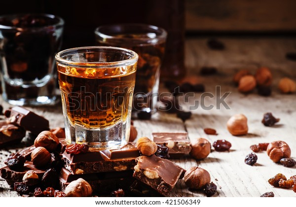 Brandy, chocolate with nuts and raisins, vintage wooden background, selective focus
