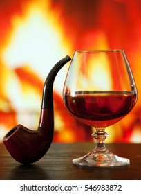 Brandy glass and smoking pipe on the table near the burning fireplace