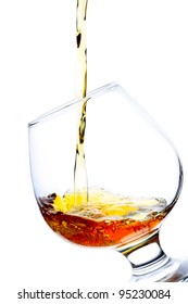 Brandy pouring into a glass isolated on white