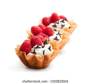 Brandy  snap baskets with ice cream and berries isolated on white