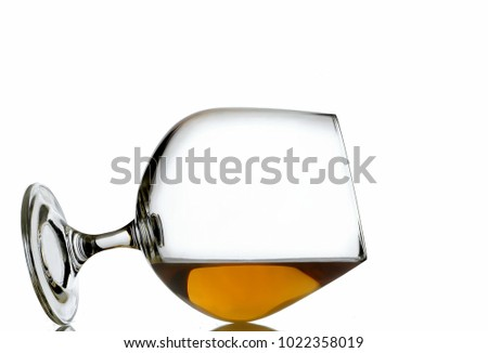 A brandy snifter laying on it's side sitting on a reflective grey surface with bright background. The brandy goes up to the edge, indicating a perfect pour. Bright field lighting used. Copy space