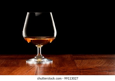 Brandy snifter on a bar top isolated on a black background
