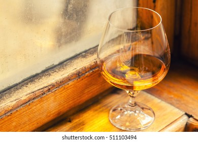 Brandy in a special snifter glass on a wood windowsill