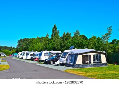 Bransgore, Hampshire / England - 6/23/2018: A row of caravans with awnings at the Caravan & Motorhome Club Site, at Bransgore in the New Forest region of Hampshire. Blue sky and trees for background.