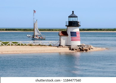 Brant Point lighthouse, with its American flag wrapped around its wooden tower, guides a sailboat out of Nantucket Island harbor in Massachusetts.