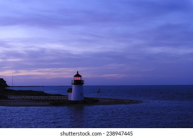 The Brant Point Lighthouse at the entrance to Nantucket Harbor at sunset. Beautiful New England travel scene at night.