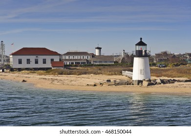 The Brant Point Lighthouse at the entrance to Nantucket Harbor with the island behind in autumn. The 26 foot tall white wooden lighthouse is the shortest in New England.
