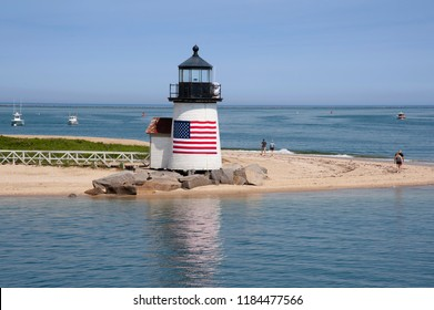 Brant Point lighthouse on Nantucket Island has an American flag wrapped around the tower greeting visitors to this Massachusetts island. It is a favorite quiet destination for tourists.