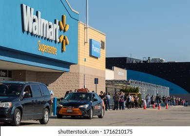 BRANTFORD, CANADA - April 8, 2020: Front of a Walmart Superstore with people lined-up outside due to the global pandemic of COVID-19 and social distancing guidelines.